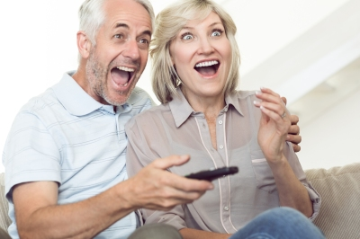 Cheerful mature couple watching tv on sofa at home